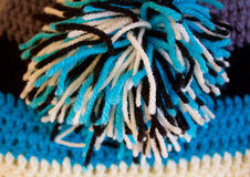 Colorful crochet hat with pompon. Detail of the pompon on the crochet baby hat Royalty Free Stock Photography