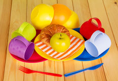 Colorful crockery, croissant and an apple on  background of light wood Royalty Free Stock Photography