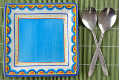Colorful crockery with old cutlery. On a green place-mat Royalty Free Stock Images