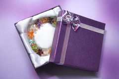 Colorful crystal bracelet in the gift box. Colorful crystal bracelet in the purple gift box royalty free stock photo