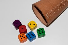 Colorful cubes in in front of a part of a leather cube mug in front view. Photographed in close up and macro as a cut out stock images