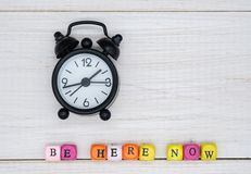 Colored cubes with text be here now and black alarm clock. Colorful cubes with the inscription be here now and black retro alarm clock. the concept of Buddhism royalty free stock images