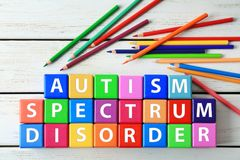 Colorful cubes and pencils on wooden background. Autism awareness concept Stock Photography