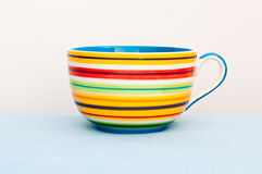 Colorful cup on blue cloth Royalty Free Stock Image
