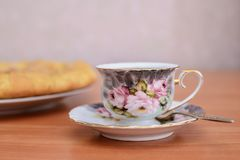 Colorful cup of tea on a saucer. Standing on the table next to the pie Royalty Free Stock Photography