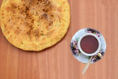 Colorful cup of tea on a saucer. Standing on the table next to the pie Royalty Free Stock Photos