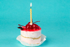 Colorful cupcake with a cherry on top. With a candle on a blue background, macro Stock Photos