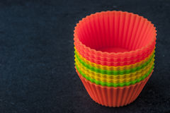 Colorful cupcake molds on the dark table Stock Photo