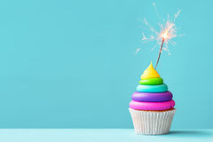 Colorful cupcake with sparkler. Brightly colored cupcake decorated with a sparkler Royalty Free Stock Image