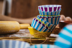 Colorful cupcake wrappers with baking pan on wooden background Stock Images