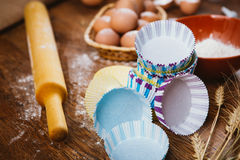 Colorful cupcake wrappers with baking pan on wooden background Royalty Free Stock Image