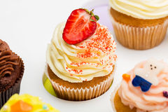 Colorful cupcakes with different Tastes. Strawberry Cupcake is in the center. beautifull cakes on white table. Close up Royalty Free Stock Photography