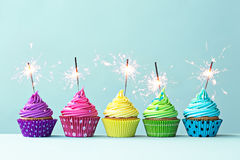 Colorful cupcakes with sparklers. Row of colorful cupcakes with sparklers
