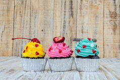 Colorful cupcakes on a wooden background Royalty Free Stock Photography