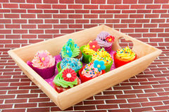 Colorful cupcakes on wooden tray Royalty Free Stock Photography