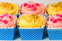 Colorful cupcakes yellow and pink. Delicious cupcakes, in a repetitive manner, in blue   and white boxes, decorated with lemon shavings and turkish delight Royalty Free Stock Image