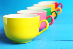 Colorful cups on blue wooden background. Royalty Free Stock Photo