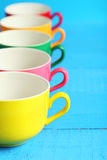 Colorful cups on the blue wooden background Stock Photo