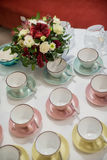 Colorful cups in front of flowers. On white stock photography