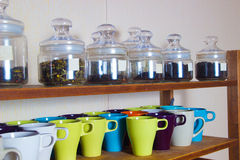 Colorful cups and a lot of varieties of tea on the shelves Stock Photos