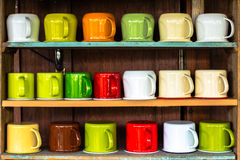 Colorful cups on shelf Royalty Free Stock Image
