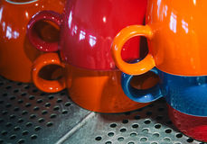 Colorful cups stacked on the surface of the coffee machine. Cups stacked upside down on the heated surface of a coffee machine in a pub Royalty Free Stock Photography
