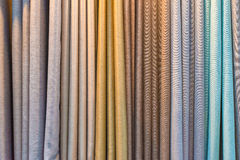 Colorful curtain samples hanging from hangers on a rail Royalty Free Stock Photo