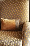 Colorful cushion on the chair. Orange decorative cushion on a chair in a guest lodge royalty free stock images
