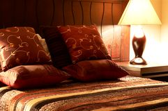 Colorful cushions on the bed. Colorful cushions on a bed with a silk bed cover in a guest lodge Stock Images