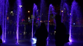 Colorful dancing fountain at night. Slow-motion closeup footage of jets of water on a dark background. Unrecognizable stock footage