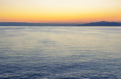 Colorful dark sunset over the sea and mountains Stock Photos