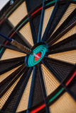 Colorful dart and target with green, yellow and red colors at th. E dartboard center Stock Photos