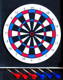 Colorful darts board close up with arrows in the row Stock Photo