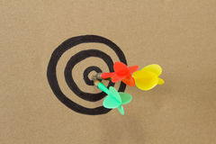 Colorful darts on center of dartboard. Red, green, and  yellow darts on center of dartboard Stock Photography