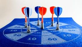 Colorful darts on a felt dart board Stock Photo