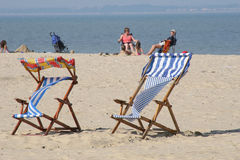 Colorful deckchairs on beach. Colorful deckchairs on a beach with holiday makers in background Royalty Free Stock Image