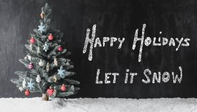 Colorful Decorated Tree, Calligraphy Happy Holidays, Let It Snow. Black Cement Background With English Calligraphy Happy Holidays, Let It Snow. Colorful royalty free stock image