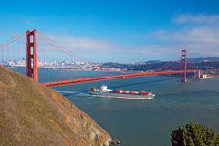Golden Gate & Cargo ship passing below Stock Images