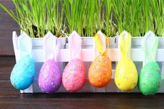 Colorful decorative eggs of rainbow colors on a background of green grass. Easter. stock image