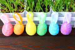 Colorful decorative eggs of rainbow colors on a background of green grass. Easter. stock images