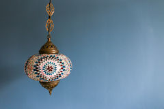 Colorful decorative hanging light against blue wall with copy space. Vintage lantern is decorated in a service hotel. Lantern is used to describe many types of royalty free stock photography