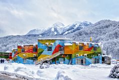Colorful decored office building of Gorky Gorod mountain ski resort. Scenic winter day landscape with snowy Aibga mountain peaks. Sochi, Russia - January 16 stock photo