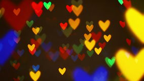 Colorful defocused blinking heart bokeh festive lights as abstract background stock footage