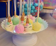 Cake pops with a unicorn themed party complete with all sorts of treats. Colorful and delicious cake pops with frosting served on a white platter on a decorated royalty free stock photo