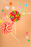 Colorful delicious jelly candies and lollipops on beige Royalty Free Stock Photos