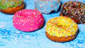 Colorful delicious sweet donuts spinning on a blue background. Slow motion video, closeup. stock footage