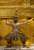 Colorful demon statue surrounding the base of a chedi. stock photos