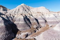 Colorful desert mountain peaks with purple, gray, and brown strata in Petrified Forest National Park, Arizona. Barren dry mountain peaks in the colorful desert stock photo