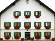 Colorful design of white house front. A white house front with green window shutters and red blooming flowers in boxes - a characteristic South Bavarian country Royalty Free Stock Photo