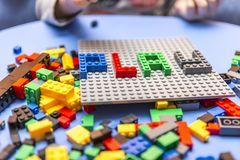 Child arranges block of constructor. a childhood game that develops the imagination of small people. Colorful designer in the hands of a toddler. fun for kids Royalty Free Stock Photography